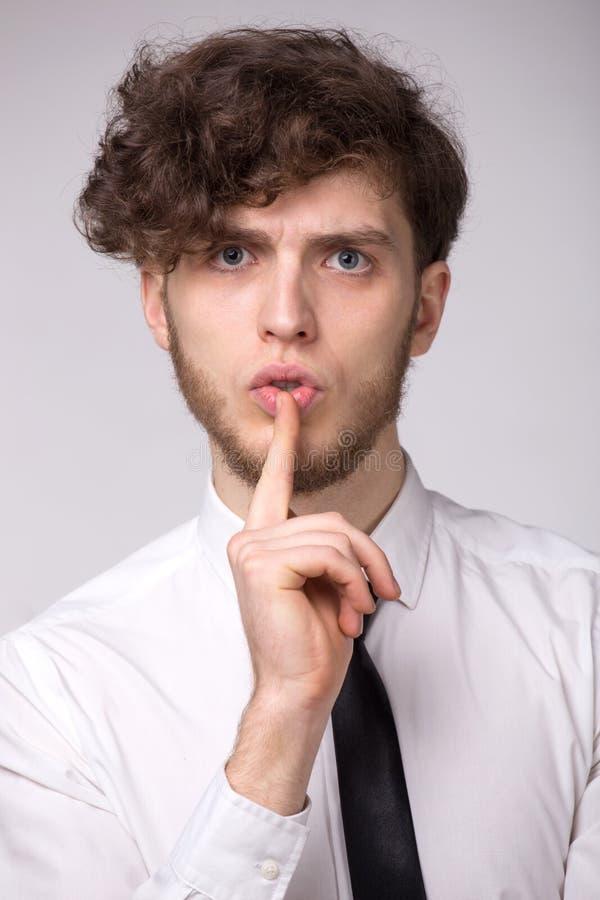 Den allvarliga unga skäggmannen håller fingret på kanter, önskar att vara komplott eller göra tystnad royaltyfria bilder