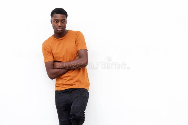 Den allvarliga unga svarta mannen i t-skjortan som poserar mot isolerad vit bakgrund med armar, korsade fotografering för bildbyråer