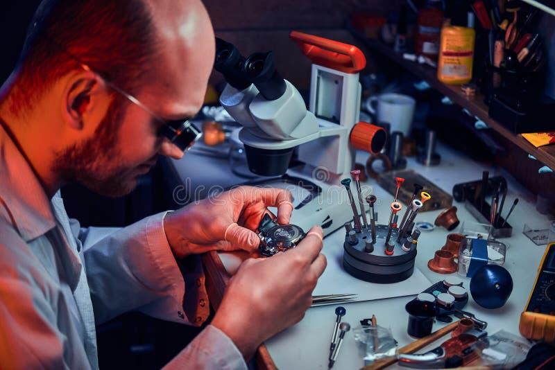 Den allvarliga urmakaren reparerar cutomers best?llning p? hans egen reparera studio arkivfoto