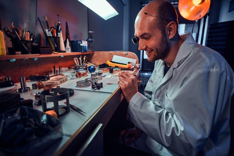 Den allvarliga urmakaren reparerar cutomers best?llning p? hans egen reparera studio arkivbilder