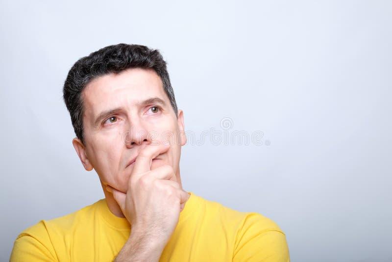 Den allvarliga vita medelåldersa mannen trycker på hans haka med hans hand och ser hänsynsfullt royaltyfria foton