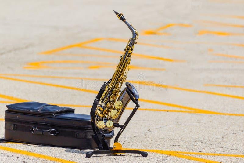 Den alt- saxofonen på att vänta på för ställning som är dess tajmar solo royaltyfria foton