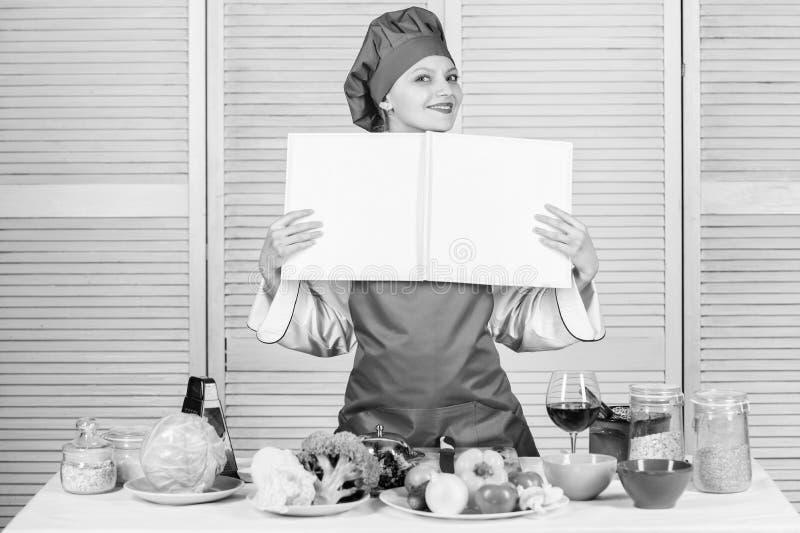 Den amat?rm?ssiga kocken l?ste bokrecept Flickan l?r recept Bok av den ber?mda kocken F?rb?ttra att laga mat expertis Bokrecept _ fotografering för bildbyråer