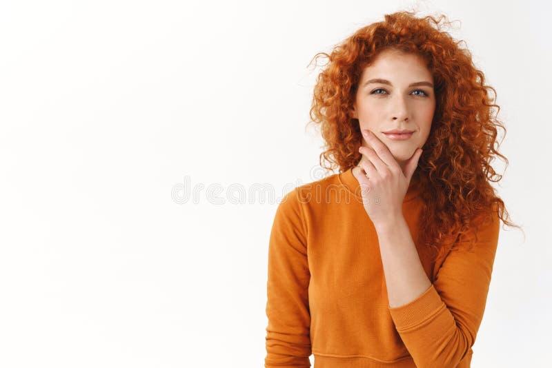 Den ambitiösa fundersamma kvinnliga rödhårig manentreprenören gnider hakan som skelar som tänkande görande intressant antagande,  arkivfoton