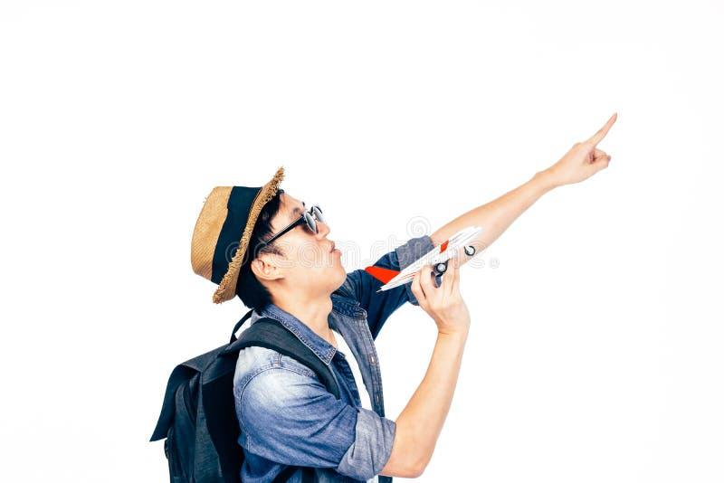 Den ambitiösa unga turisten som upp till pekar himlen som drömmer för att resa, isolerade över vit bakgrund royaltyfri fotografi