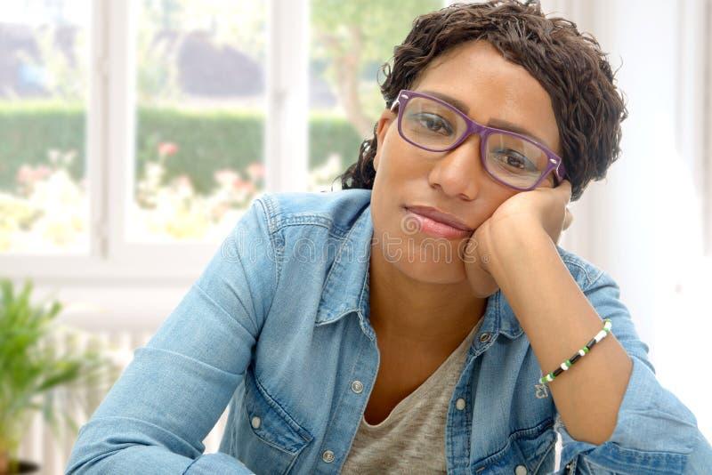 Den amerikanska afrikanska affärskvinnan tröttade i hans kontor fotografering för bildbyråer