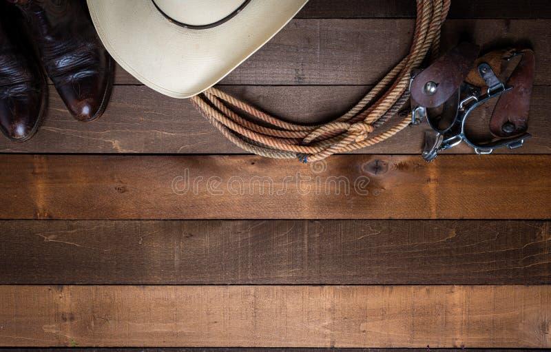 Den amerikanska cowboyen Items som incluing en lasso, sporrar och en traditionell sugrörhatt på en träplankabakgrund royaltyfri fotografi