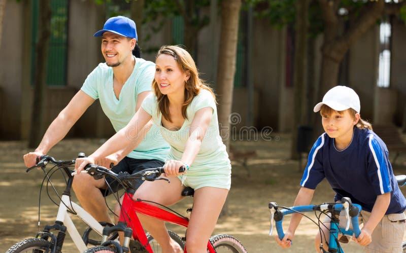 Den amerikanska familjen som in cyklar, parkerar royaltyfria foton