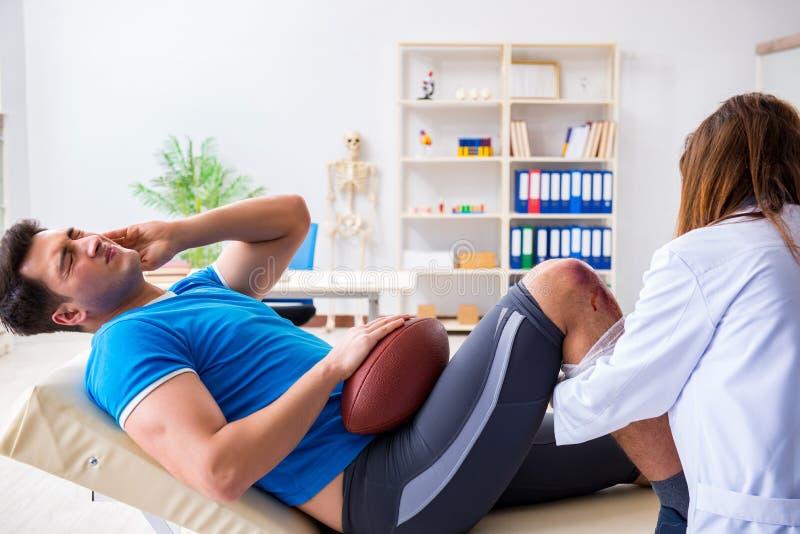 Den amerikanska fotbollsspelaren med skada som besöker doktorn royaltyfri fotografi
