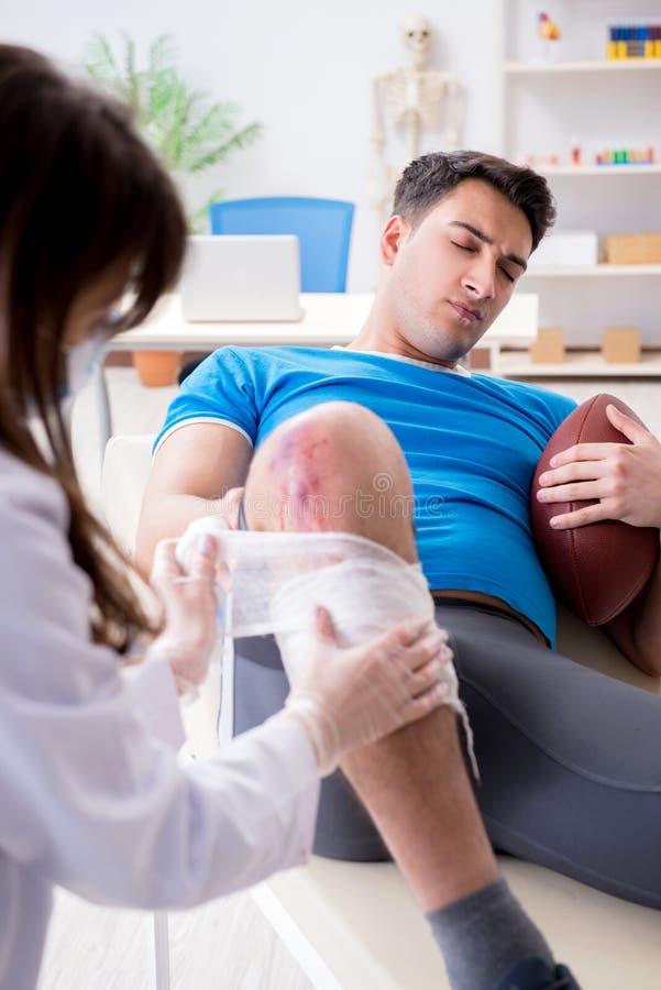 Den amerikanska fotbollsspelaren med skada som besöker doktorn royaltyfri bild