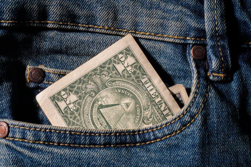 Den amerikanska pengardollaren i jeans stoppa i fickan grov bomullstvillbakgrundstext arkivfoto