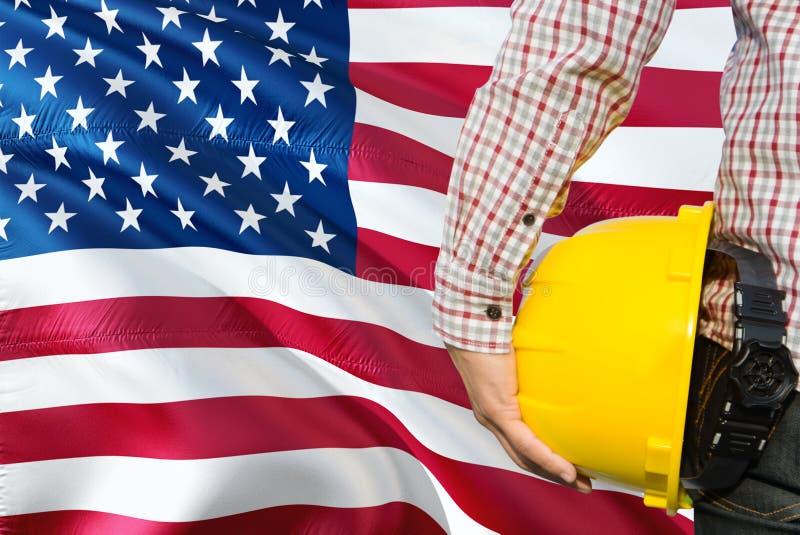 Den amerikanska teknikern rymmer den gula säkerhetshjälmen med vinkande Amerikas förenta stater sjunker bakgrund Konstruktion och arkivfoto