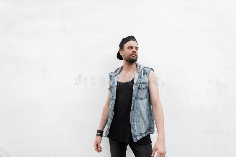 Den amerikanska unga mannen som hipsteren i en T-tröja i en grov bomullstvill tilldelar jeans i ett trendigt svart lock med ett s royaltyfria bilder
