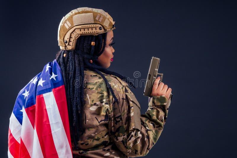 Den amerikanske arméns latinsoldat i kamouflage kläder, hårlås kvällssmatning och stora läppar som håller ett vapen på arkivfoto