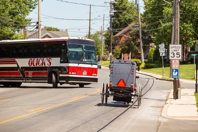 Den Amish barnvagnen och turnerar bussen arkivbilder