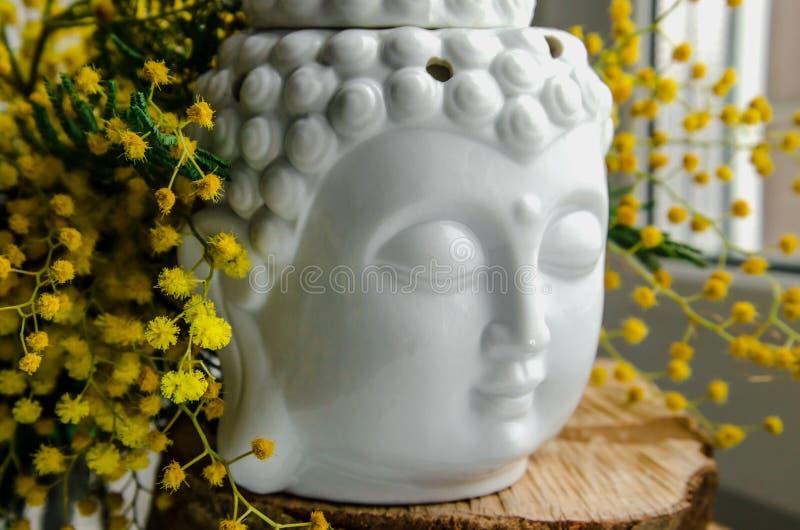 Den andliga rituella meditationframsidan av Buddha på trä, den hem- dekoren, mimosagulingvår blommar 1 livstid fortfarande arkivbilder