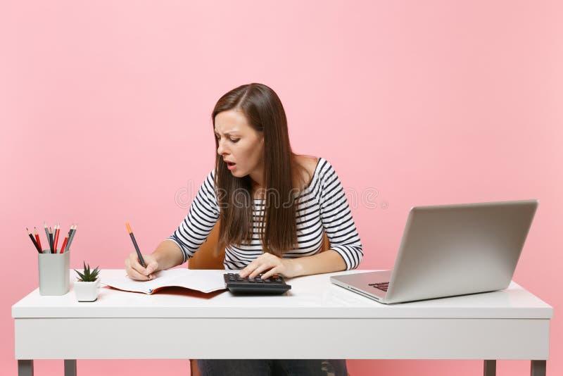 Den angångna kvinnan som använder räknemaskinen som skriver anmärkningar med beräkningar, sitter och arbetar på kontoret med den  arkivbild