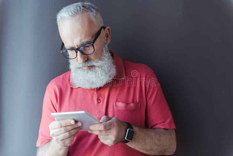 Den angenäma höga mannen i exponeringsglas använder den moderna apparaten arkivfoton