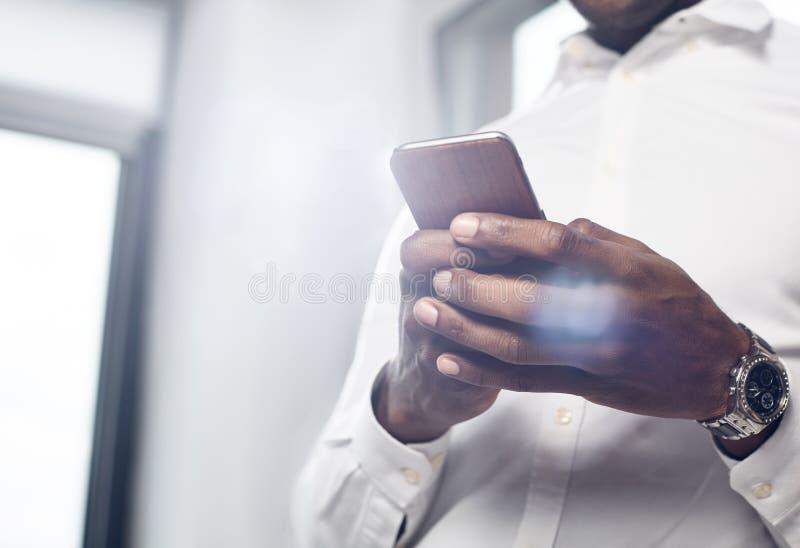 Den angenäma unga mannen använder smartphonen arkivfoto