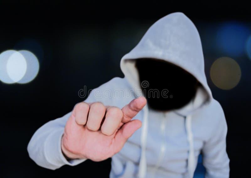 Den anonyma brottsliga mannen i huv av staden tänder framme royaltyfri foto