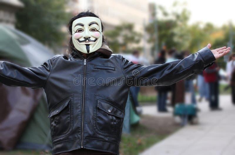 den anonyma dc-maskeringen upptar personen som protesterar royaltyfri foto