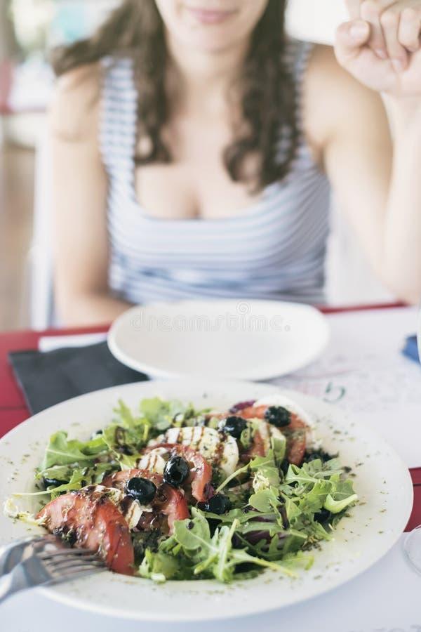 Den anonyma kvinnan som är klar för, äter sallad i restaurang royaltyfria bilder