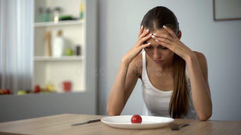 Den anorektiska flickan känner sig yr, uttömt av strängt bantar, den utmattade kroppen, svält arkivbild