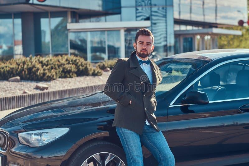 Den ansade attraktiva mannen lutar p? hans egen bil p? parkeringen royaltyfri foto