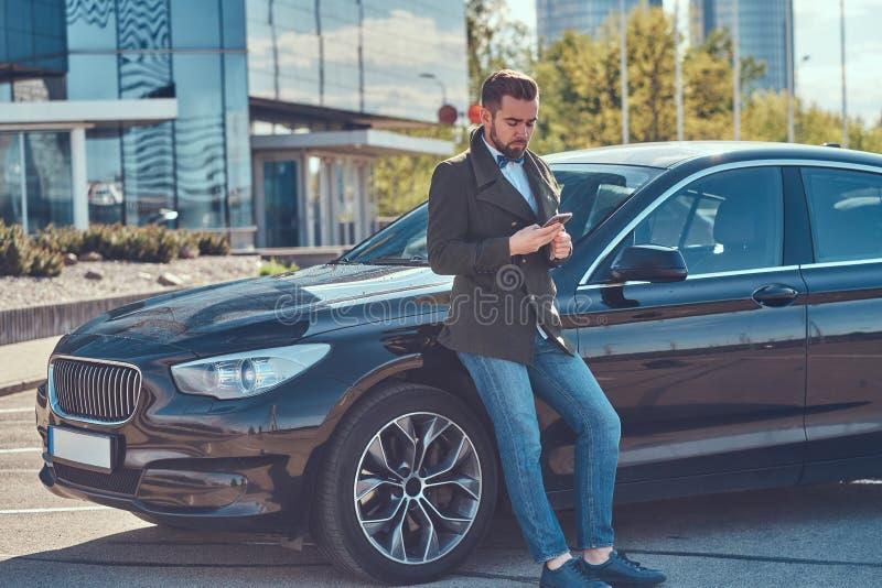 Den ansade attraktiva mannen lutar p? hans egen bil p? parkeringen arkivfoto