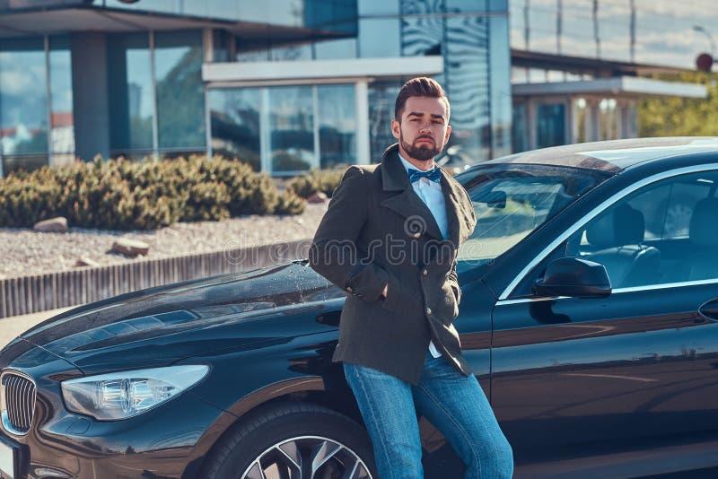 Den ansade attraktiva mannen lutar p? hans egen bil p? parkeringen arkivfoton