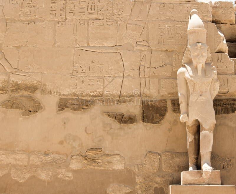 Den antika skulpturen av Pharaoh mot bakgrund av en stenvägg med egyptiska hieroglyfer och tematiska ritningar arkivbild