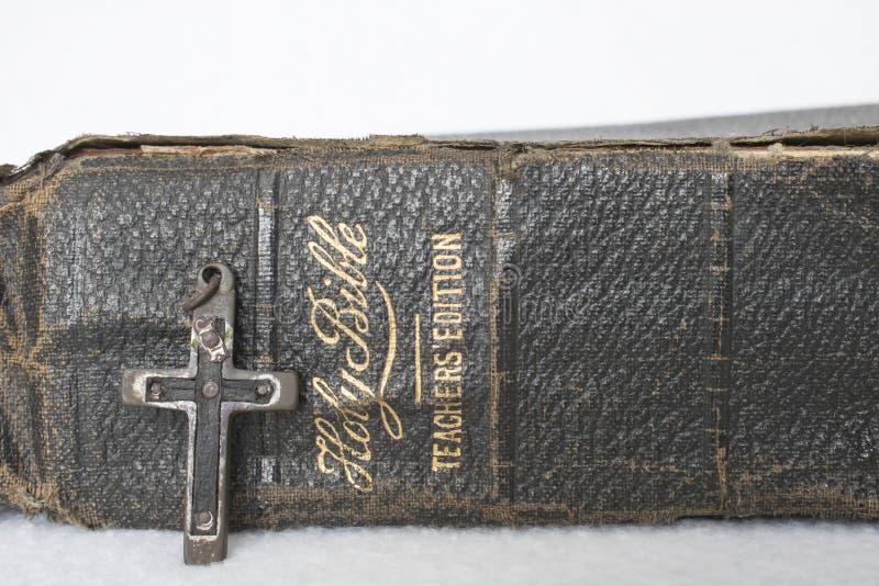 Den antika slitna läderbibeln med antikvitetkorset av Wood metall spikar royaltyfria foton