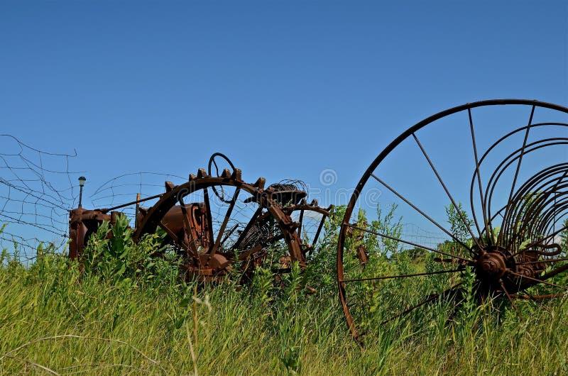 Den antika traktoren och förrådsplatsen krattar royaltyfri bild