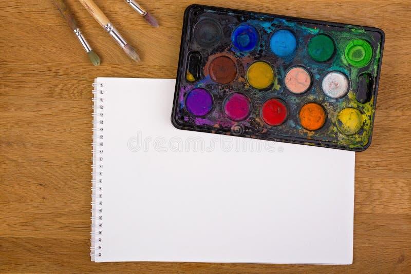 Den använda vattenfärgen målar, borstar för att måla och tomt vitbokark på träbakgrund Top beskådar royaltyfri fotografi