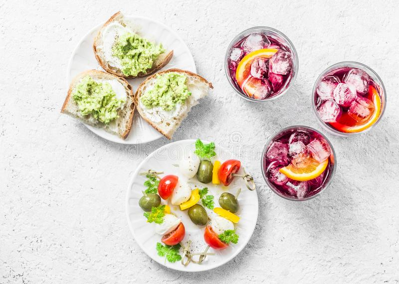 Den Aperitiv tabellen - välj och mellanmålet, bästa sikt Smörgåsar med avokadot, canapé med mozzarellaen, tomater, oliv royaltyfria foton