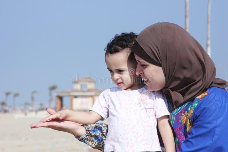 Den arabiska egyptiska muslimmodern med hennes behandla som ett barn flickan på stranden i Egypten arkivbild