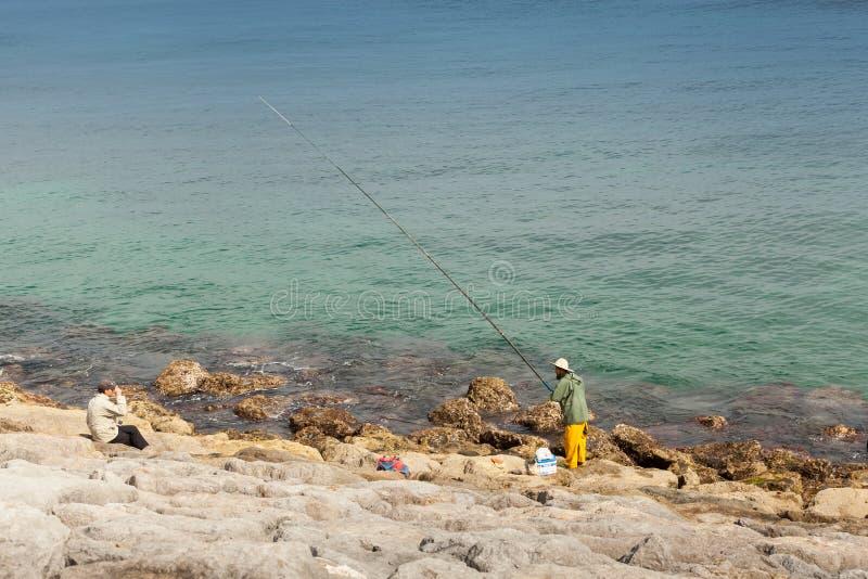 Den arabiska fiskaren med en lång stång står på kusten av Atlantic Ocean royaltyfri bild