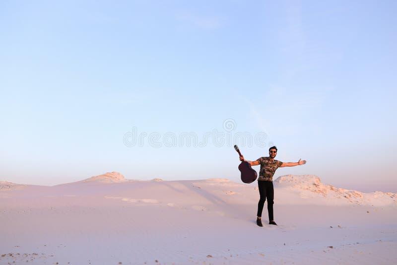 Den arabiska grabben går inspirerad vid skönhet av öknen och spelar gitarrstri fotografering för bildbyråer