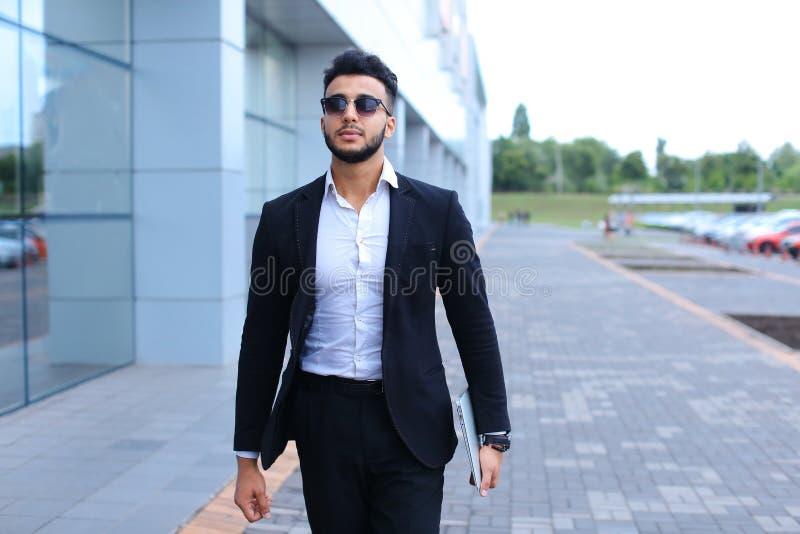 Den arabiska grabben i affärsmitt står le att gå som är långsamt royaltyfri fotografi
