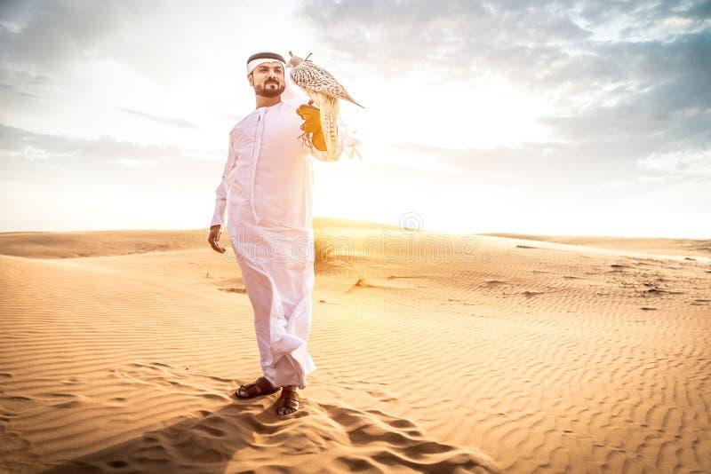 Den arabiska mannen med traditionella emirater beklär att gå i det dese royaltyfri bild