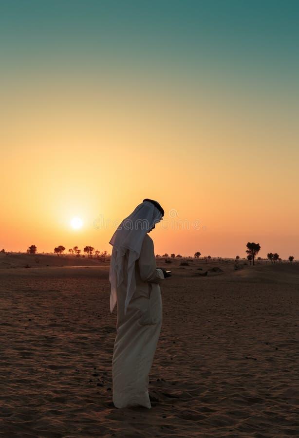 Den arabiska mannen står bara, i öknen och att hålla ögonen på solnedgången arkivfoton