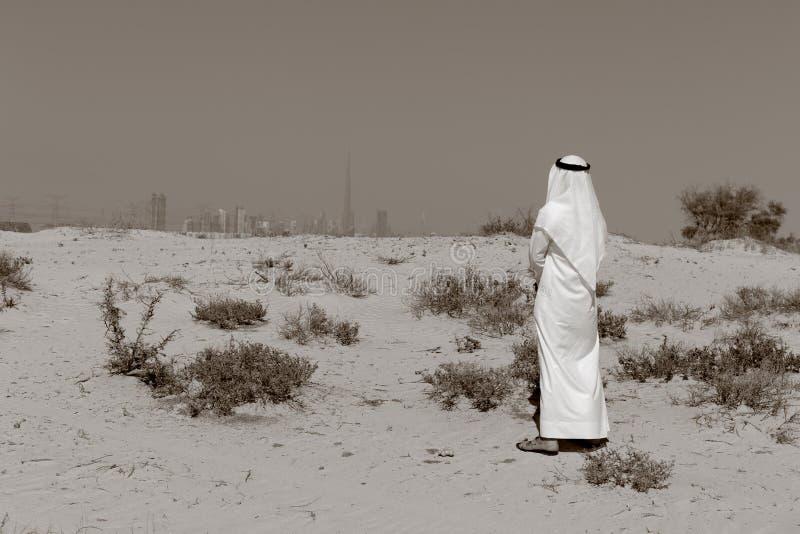 Den arabiska mannen står i öknen royaltyfri fotografi