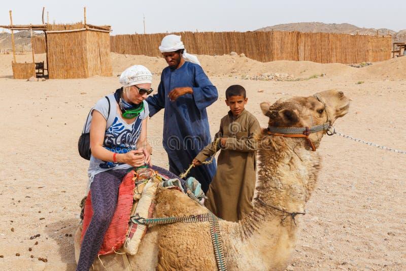Den arabiska pojken rullar turister på en kamel royaltyfria foton