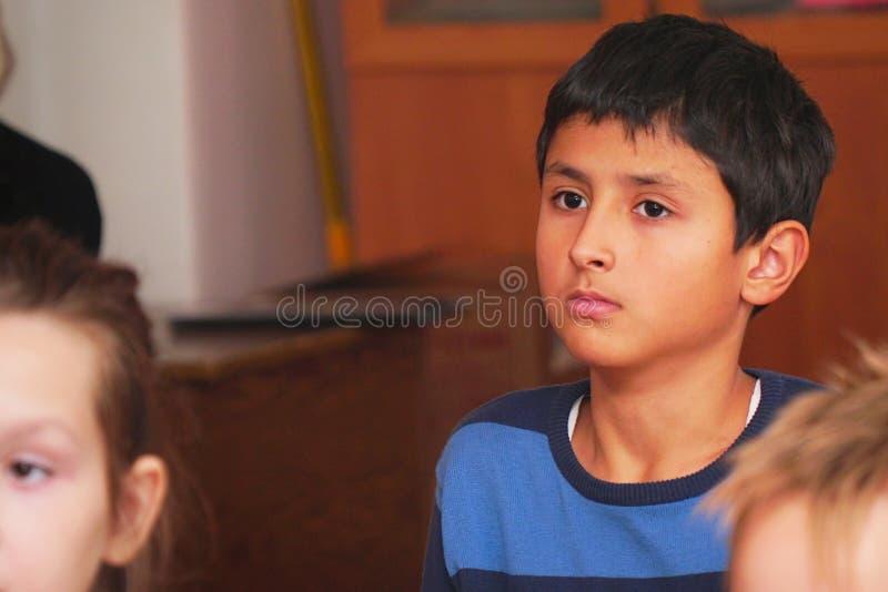 Den arabiska skolpojken i klassrumet lyssnar till läraren royaltyfria bilder