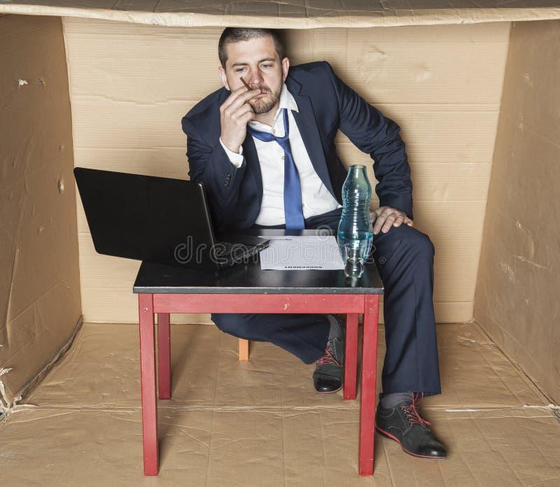Den arbetslösa affärsmannen röker och dricker alkohol arkivfoton