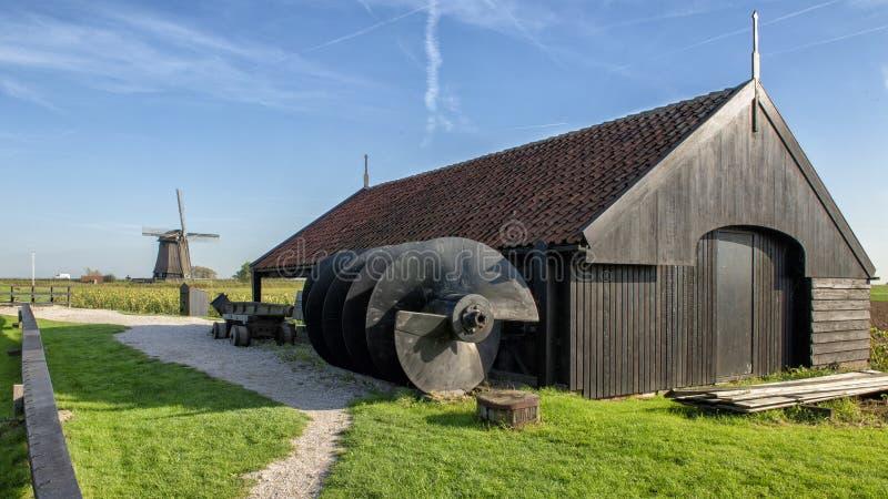 Den Archimedes skruven, lagringshuset och väderkvarnen vid det Schermerhorn museet maler, Stompetoren, Nederländerna royaltyfri fotografi