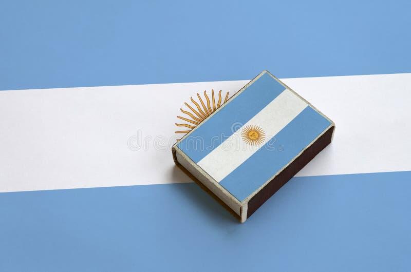 Den Argentina flaggan föreställas på en tändsticksask som ligger på en stor flagga royaltyfri fotografi
