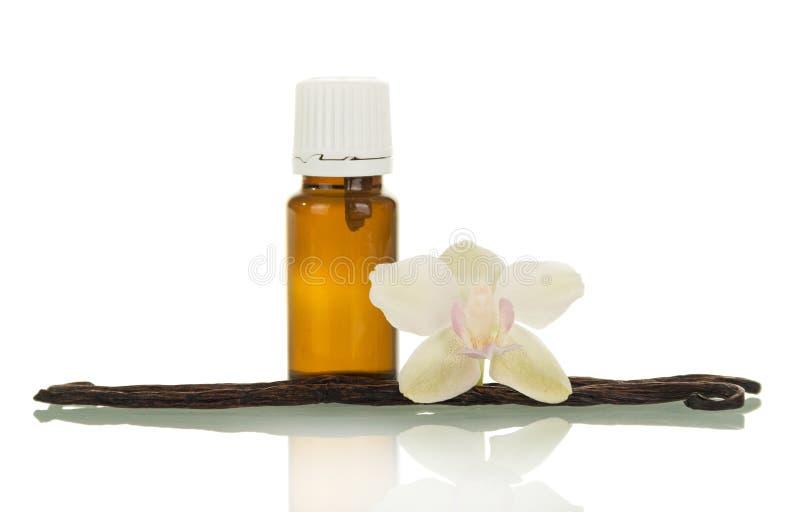 Den aromatiska flytanden för vaping, vaniljfröskidor och orkidéblomman som isoleras på vit fotografering för bildbyråer