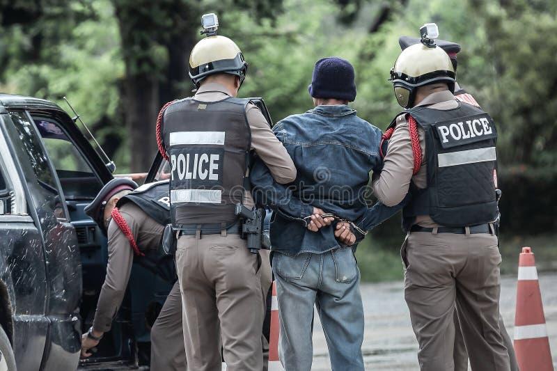 Den arresterade polisen, handfängslat, begick en anstöt, den selektiva fokusen, oväsen arkivfoto