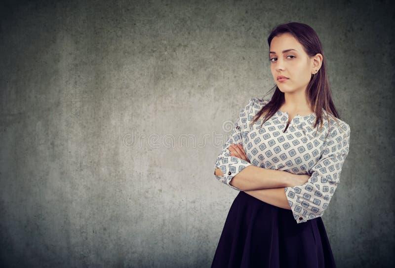 Den arroganta unga kvinnan med armar korsade arkivfoto